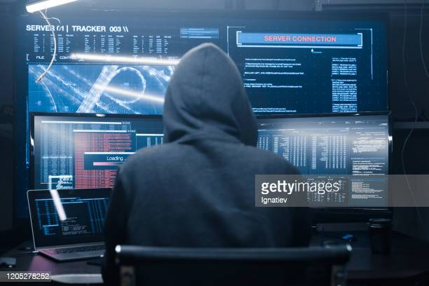 computer hacker coding on keyboard on a background of monitors. - hacker stock pictures, royalty-free photos & images