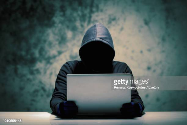 computer hacker holding laptop - computer hacker stock pictures, royalty-free photos & images