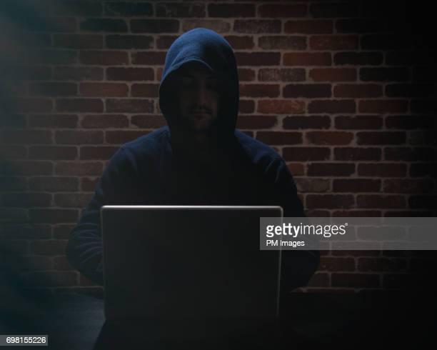 Computer hacker using lap top