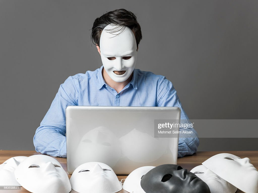 Computer hacker wearing a mask using computer : Stock Photo