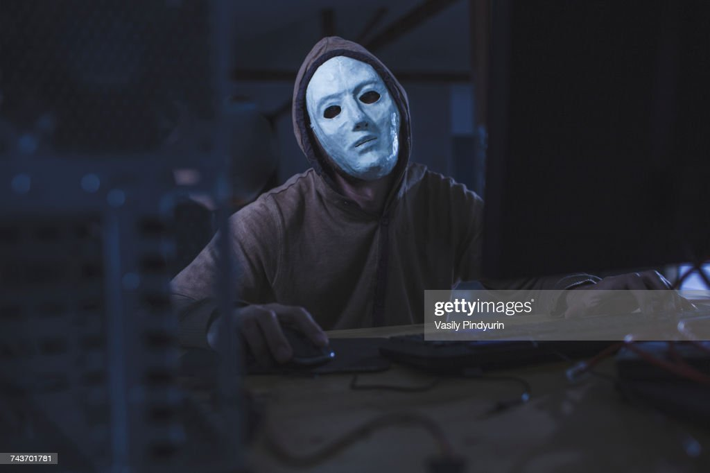 Computer hacker wearing mask and hood using computer while sitting at table : Stock Photo