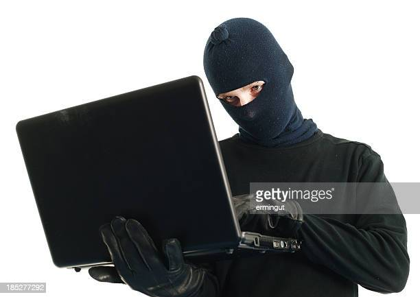 Computer hacker with mask looking at screen