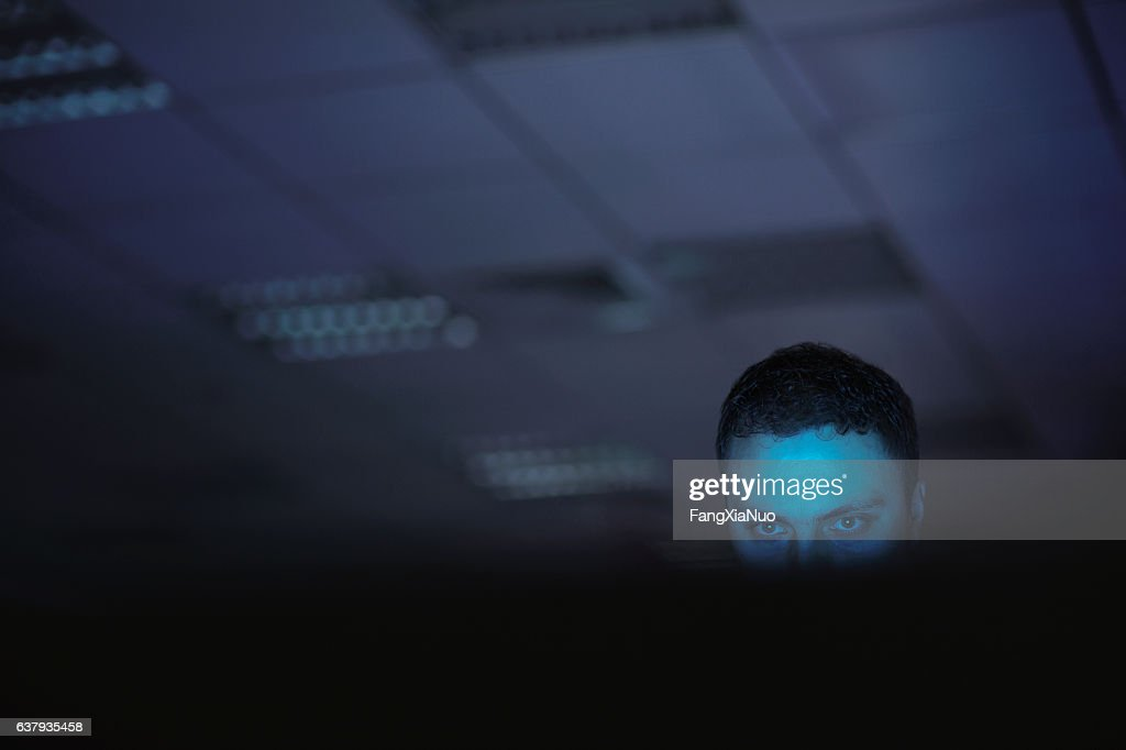 Computer hacker working on laptop late at night in office : Stock Photo