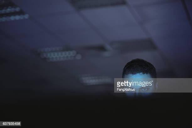 Computer hacker working on laptop late at night in office