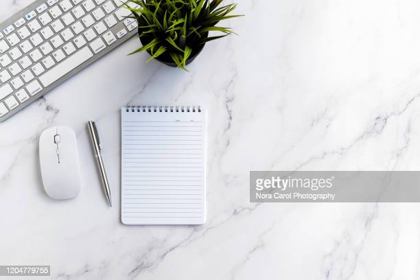 computer keyboard, potted plant, notepad and pen on marble table - table top shot stockfoto's en -beelden