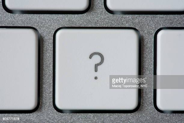 Computer keyboard with a key with a question mark.