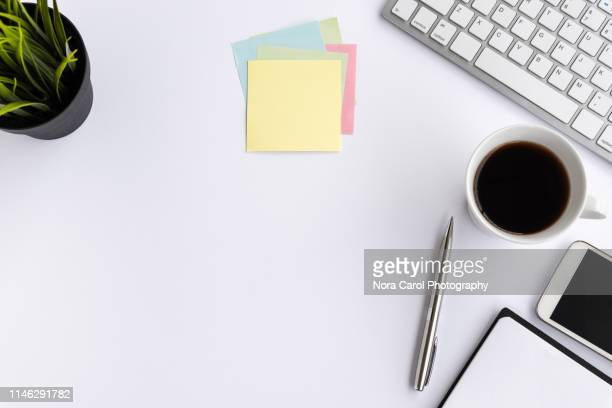computer keyboard with coffee, smart phone, pot of plant and office supply on white background - bureau stockfoto's en -beelden