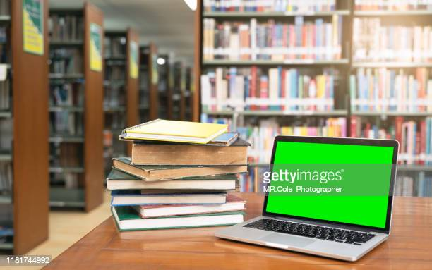 computer laptop with green screen and book stack in library room.education background concept - literature stock pictures, royalty-free photos & images