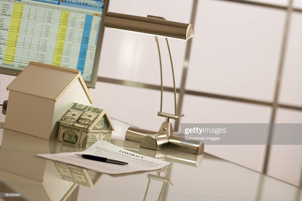 Computer, model houses, money and contract on desk : Foto de stock