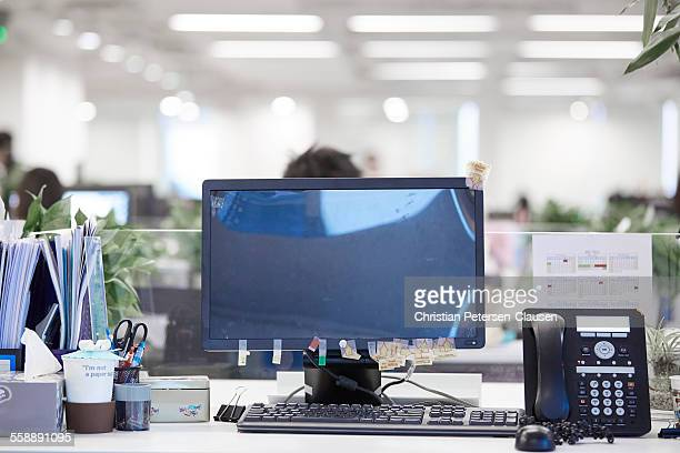 Computer monitor and phone at empty office desk