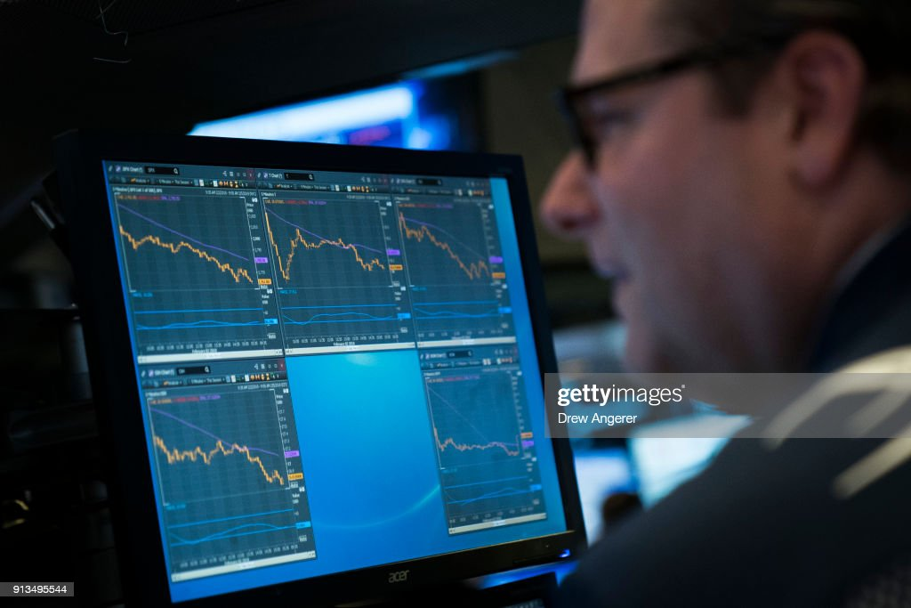 A computer monitor displays the day's numbers as traders and financial professionals work on the floor of the New York Stock Exchange (NYSE) at the closing bell, February 2, 2018 in New York City. The Dow dropped 250 points at the open on Friday morning. The Dow plunged over 660 points on Friday, marking its biggest one day plunge since June 2016 following the Brexit vote.