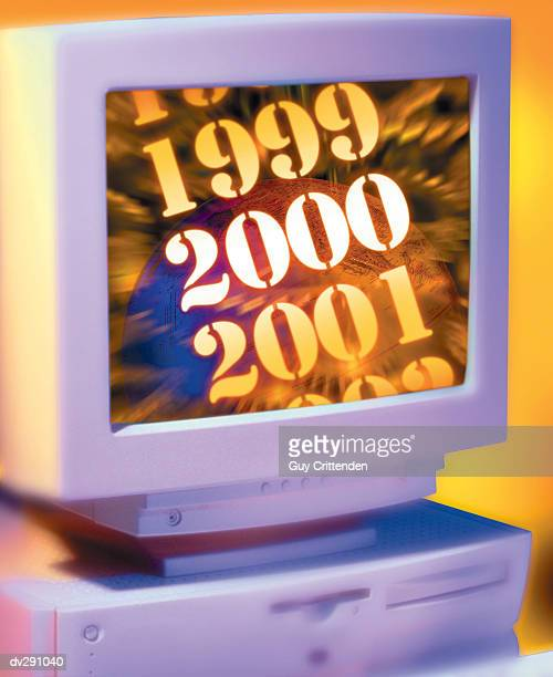 Computer monitor showing glowing year 2000 in front of globe