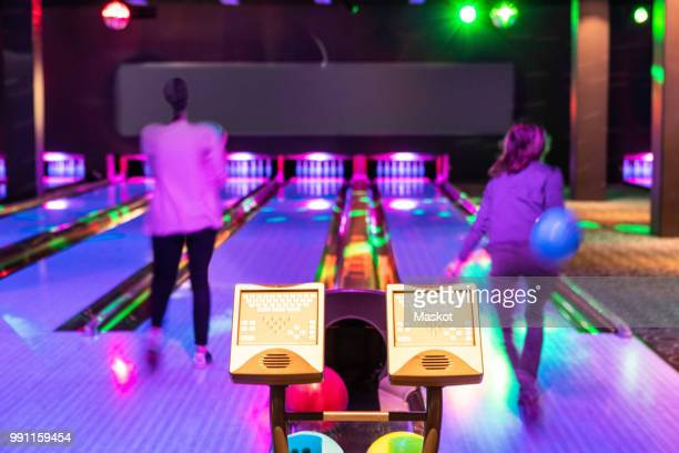 computer monitors against teenage girls throwing balls on parquet floor at bowling alley - bowling stock pictures, royalty-free photos & images