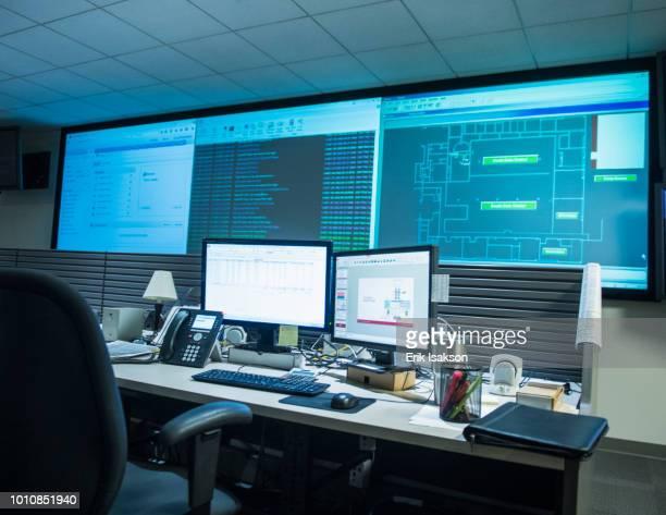 computer monitors and desk in network server control room - kontrollraum stock-fotos und bilder