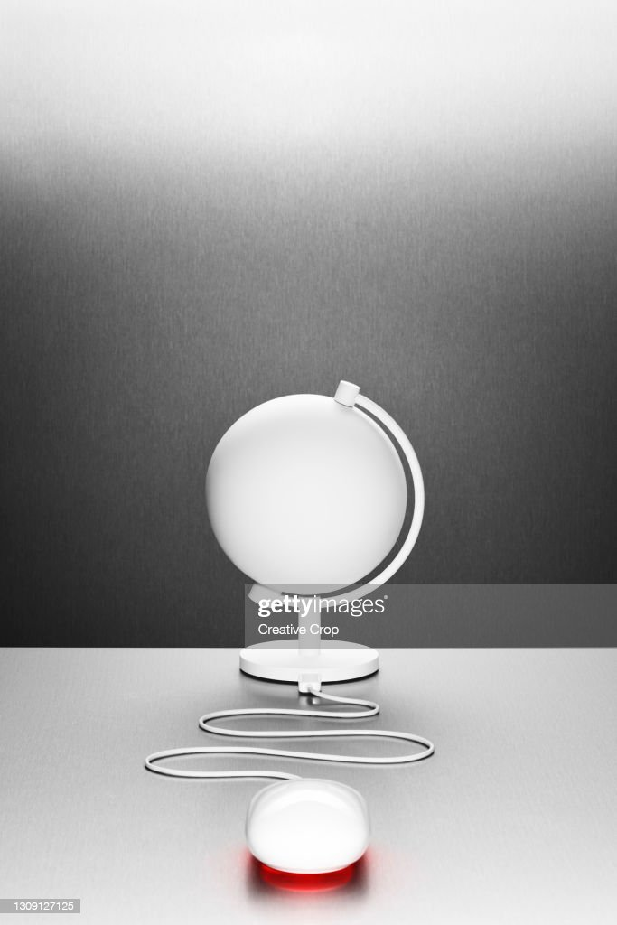 A computer mouse connected to a white desk globe : Stock Photo