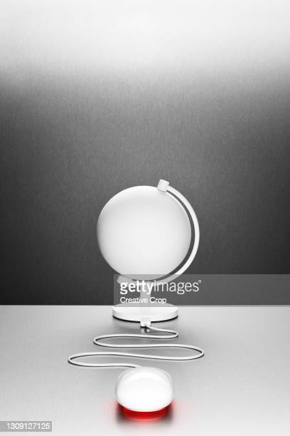a computer mouse connected to a white desk globe - microzoa stock pictures, royalty-free photos & images