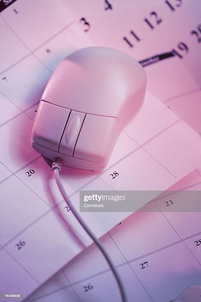Computer mouse on top of desktop calendar pages : Stockfoto