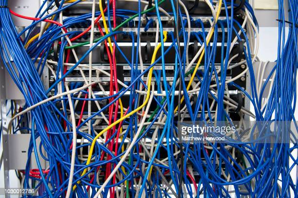 Computer network server cabinet with a mess of tangled blue coloured network cables on November 22, 2017 in Cardiff, United Kingdom.