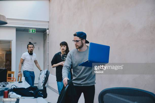 Computer programmer holding laptop while walking with colleagues in office