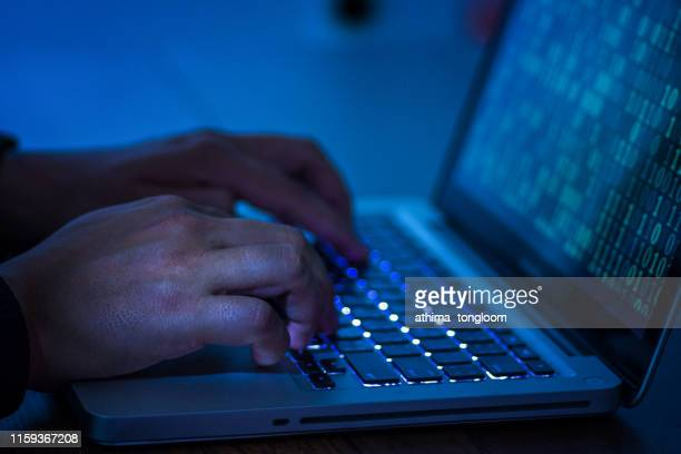 a computer programmer or hacker prints a code on a laptop keyboard to break into a secret organization system. - fraud stock pictures, royalty-free photos & images