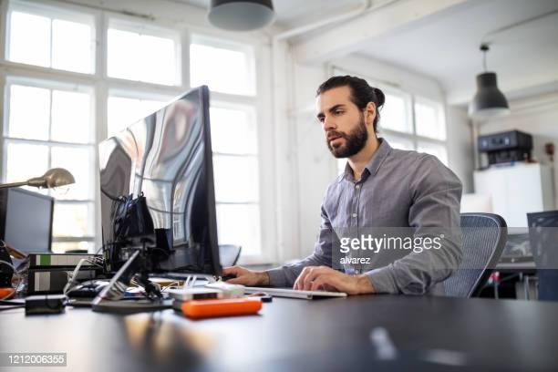 computer programmer working at his desk - desktop pc stock pictures, royalty-free photos & images