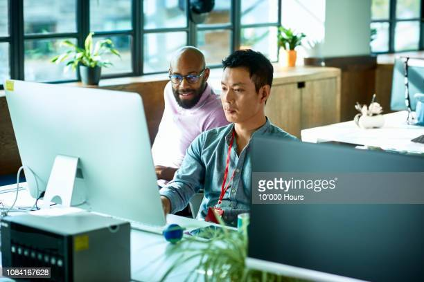 computer programmer working with male colleague in office - creative occupation stock pictures, royalty-free photos & images