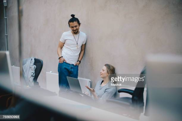 computer programmers discussing over laptop against wall in office - focus on background stock pictures, royalty-free photos & images