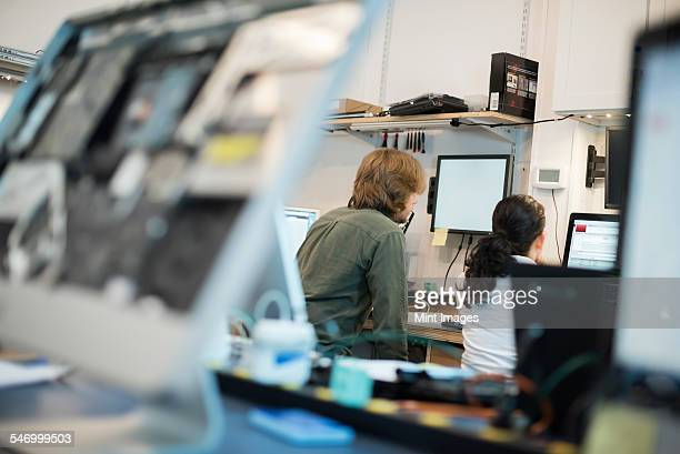 Computer Repair Shop. Two people seated using screens, and computer monitors in various stages of repair.