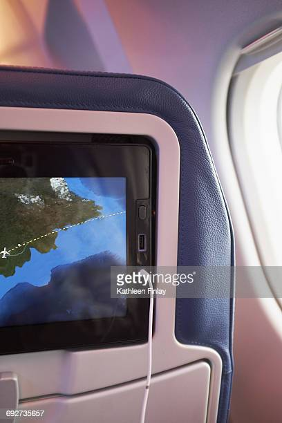 Computer screen route map on back of airplane seat