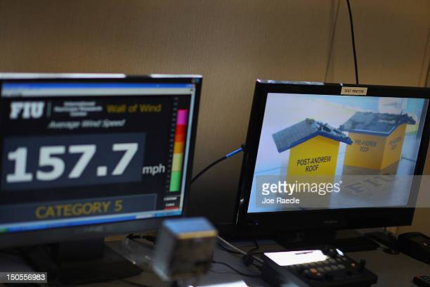Computer screen shows 157.7 mph wind speed as two structures are tested in front of twelve fans that create what is called a Wall of Wind, at the...