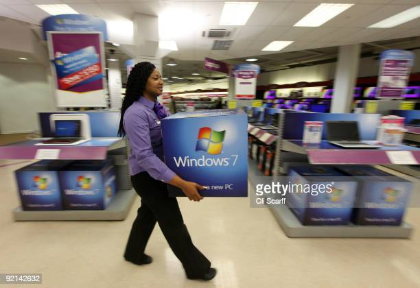 A computer store employee carries promotional signage for Microsoft's new operating system 'Windows 7' ahead of its official launch at midnight...