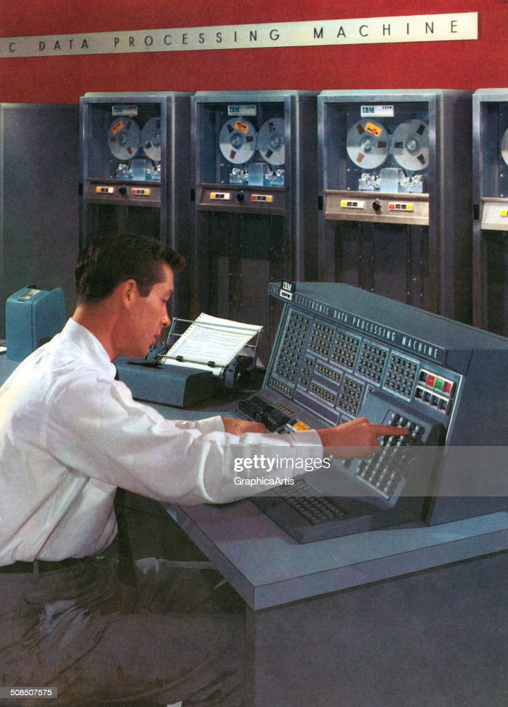 A computer technician operates a computer console in a room filled with early computers, IBM's Electronic Data Processing Machine, 1950s. Screen print from a photograph.