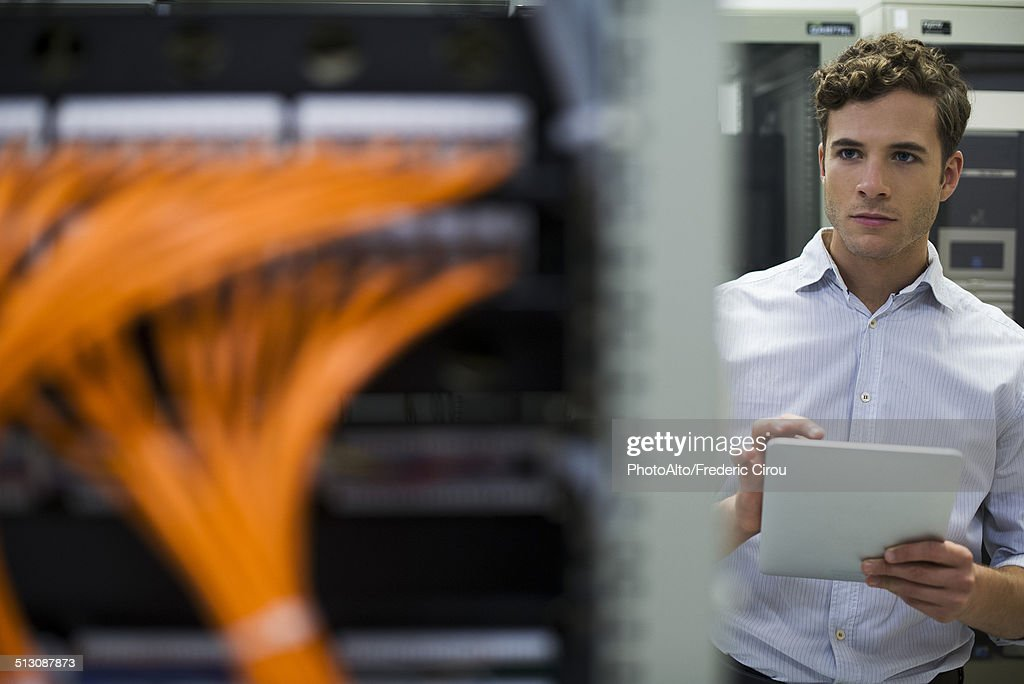 Computer technician using digital tablet performing maintenance check of mainframe equipment : Stock Photo