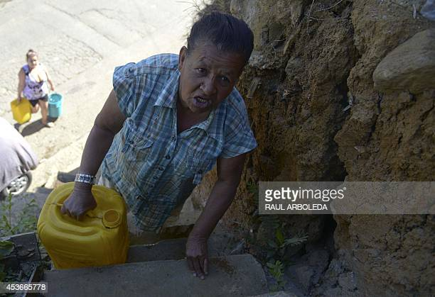 Comuna 8 shantytown resident Maria Aristizabal holds a jerry after collecting water at a communal tank up on a hill in the slum on the outskirts of...