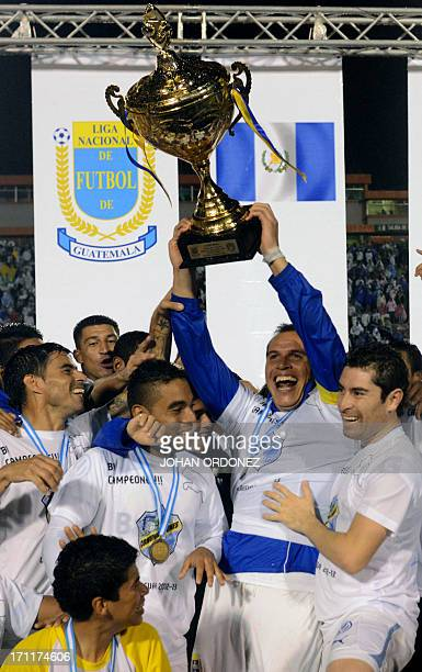 Comunicaciones players celebrate with the trophy after winning the 2013 Closing Tournament final football match against Heredia at Cementos Progreso...