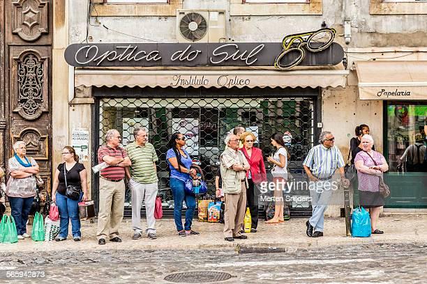 Comutors waiting for bus at optician