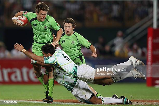 Con Foley of Australia is tackled by Robert Ebersohn and Renfred Dazel of South Africa during Day Three of the IRB Dubai Sevens at the Sevens Stadium...