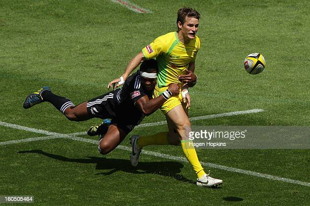 Con Foley of Australia passes in the tackle of Lote Raikabula of the All Blacks Sevens in the quarterfinal cup match between New Zealand and...