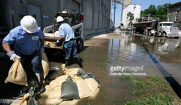 Conagra Foods mill maintenance workers Bill Bechtold and Jim Hand pile sandbags around a hole that is contributing to the leaking basement at the...