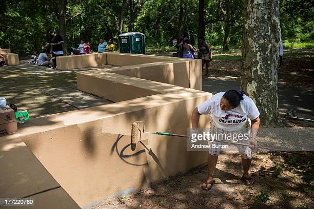 Concempcion Gutierrez a volunteer paints over a grafittied structure in Farnham Park during a day of action organized by Camden County Police...