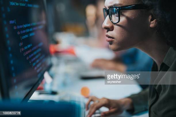 concentrated african american programmer reading computer codes on desktop pc. - problems stock pictures, royalty-free photos & images