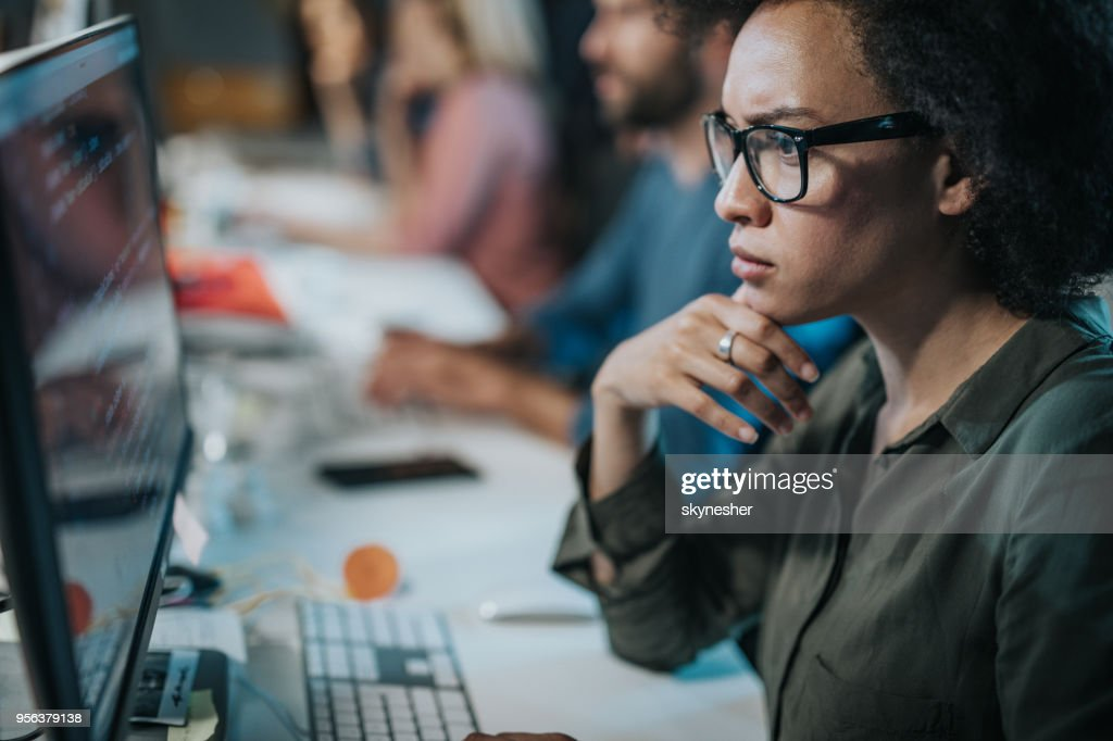 Concentrated African American woman brainstorming while coding data on desktop PC. : Stock Photo