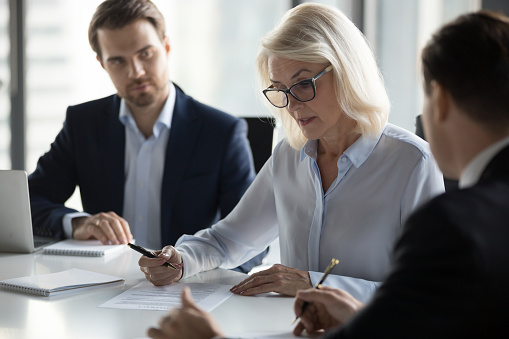 Concentrated aged businesswoman checking agreement before signing 1092087526