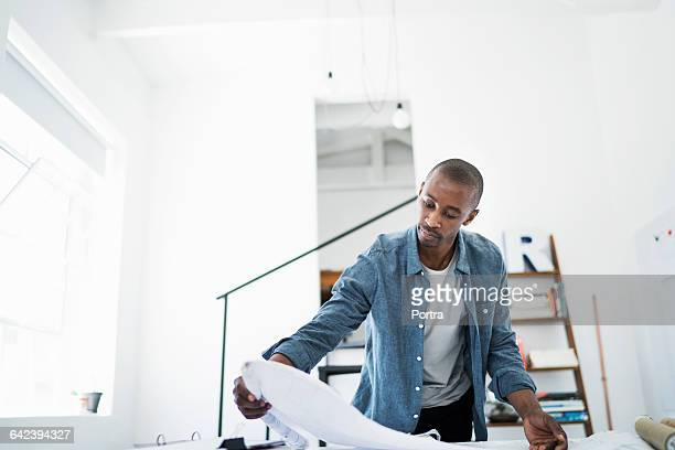 concentrated architect reviewing blueprints - fully unbuttoned stock pictures, royalty-free photos & images