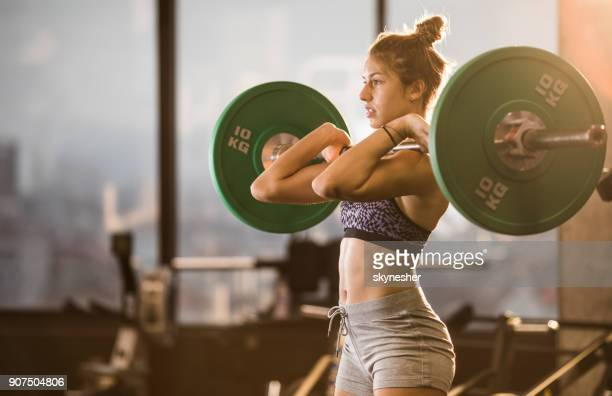 Concentrated athlete having strength training with barbell in a gym.