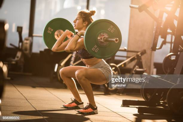 concentrated athlete having strength training with barbell in a gym. - barbell stock pictures, royalty-free photos & images