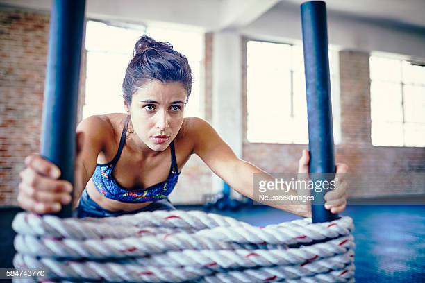 Concentrated athlete pushing battling rope sled in gym