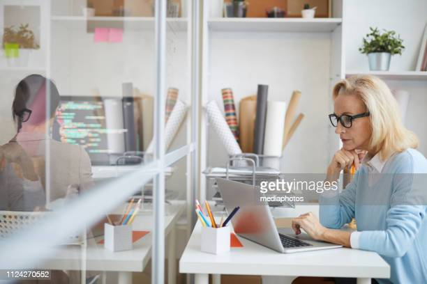 Concentrated attractive mature lady in glasses sitting at desk and leaning head on hand while using laptop and checking information