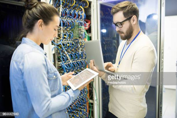 Concentrated bitcoin mining farm experts testing new hardware equipment of supercomputer using modern devices in server room