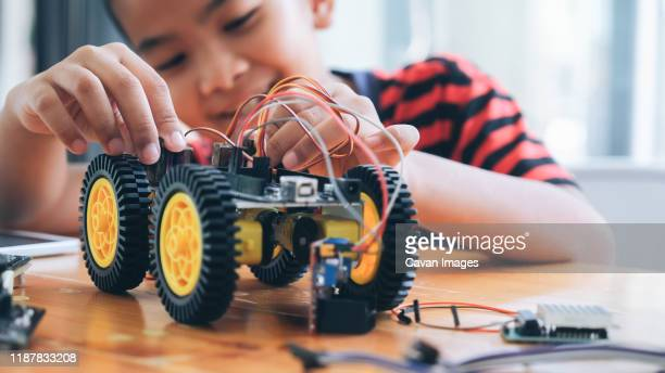 concentrated boy creating robot at lab. - remote controlled car stock pictures, royalty-free photos & images